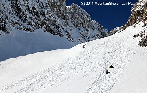 Dva snowboardisti se hrabou vzhůru laviništěm