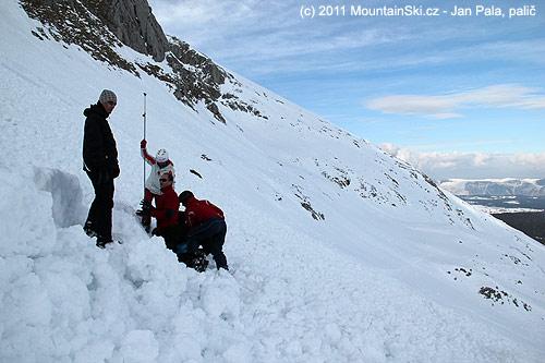 Vpoměrně čerstvém laviniště, dohledává se první zasypaný