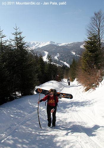 Jana si nese snowboard napříč a opírá se očerstvě ulomenouvětev