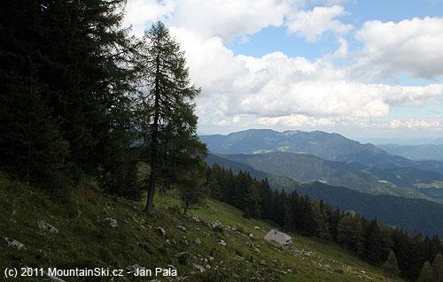 Výhled na planinu Arta a chatu se začátku lesa