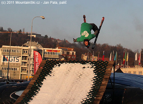 Freeskier po rozjezdu snavijákem ve vzduchu nad nafukovací matrací