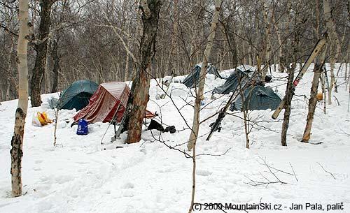 Sněhem posypaný tábor nad potokem