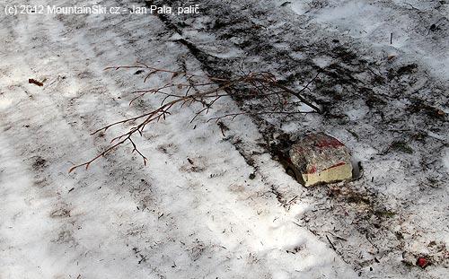 Hraniční kámen poškozený rolbou upravující běžkařskoutrať