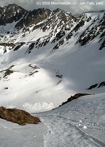 Výsledek pádu oněco větší sněhové koule, ze širokého pruhu svahu ujela povrchová měkká mokrá vrstvasněhu