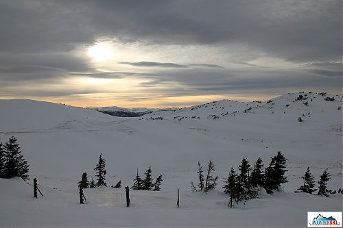The sun is partially covered by clouds over Jahorina