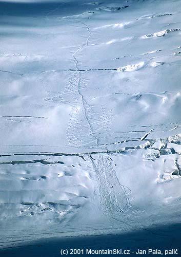 Pohled od prvního výškového tábora na moréně Leninova ledovce na dolní část severní stěny Piku Lenina, lavinové dráhy vznikly napravo od výstupové stopy pod velkou trhlinou
