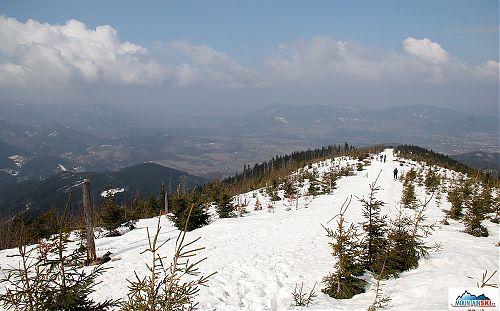 V údolích je jaro, na hřebenu spousta sněhu a částečně pod sněhem je i vrcholová část Ondřejníku na pozadí