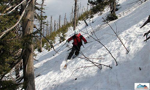 Starší bruder na telemarkových lyžích dole kopcom
