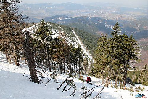 Starší bruder na telemarkových lyžích dole kopcom, na pozadí Ondřejník