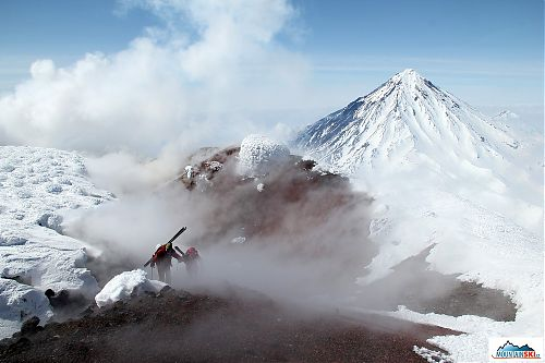Roman & Matúš climbing through fumarole at the top of volcano Avachinsky, volcano Koryaksky in the background