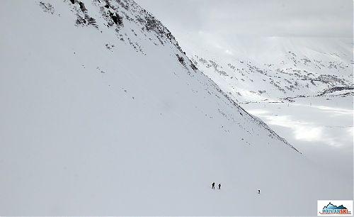Skialpinisti v dolní části výstupu na Viljučinskij, vzadu v údolí most přes řeku Paratunka