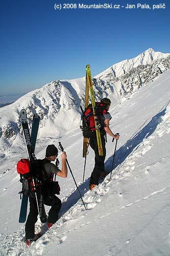 Připevnění širokých lyží bokem na batoh, výstup na Predné Solisko
