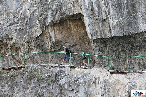 Ve skalní stěně nad vodou je vysekaná přibližně pět kilometrů dlouhá stezka