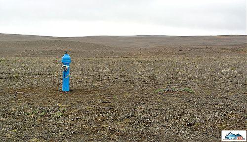 Nepochopitelně umístěný hydrant uprostřed štěrkové pouště