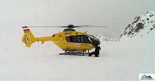 Vrtulník startuje, maník ze Söldenu zakleknul vepředu