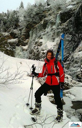 Poponášení lyží při přechodu přes potok v místě s ledopády