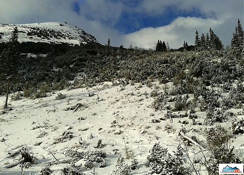 Jedna z nejnezasněženějších částí sestupu ze Smutneho, lyže neseme přes rameno, spoléháme na boty a hůlky, neboť pod malou vrstvou sněhu bývá místy velmi kluzký povrch