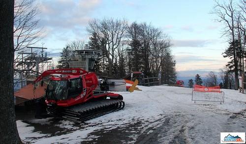 Rolba zaparkována u koncové stanice sedačky, sněhu není nejvíce