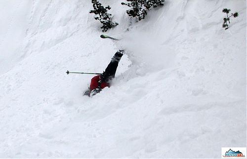 Kinetická energie způsobená nečekaným pádem způsobuje víceméně samovolnou rotaci lyžaře přes záda a batoh