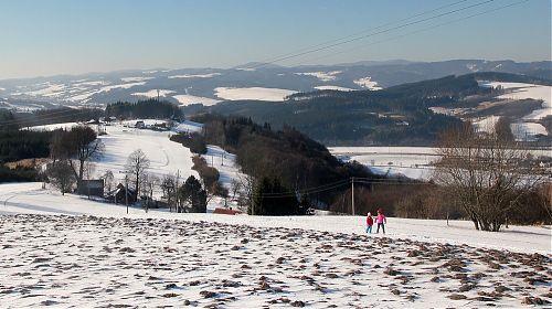 Výhled směrem na údolí říčky Ratibořka, sníh z oraniště v popředí byl větrem přesunut dále
