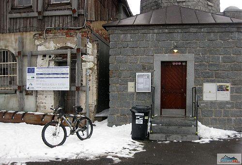 Ostudný stav budov na Klínovci konstrastuje s bíle zářící dotační cedulí EU