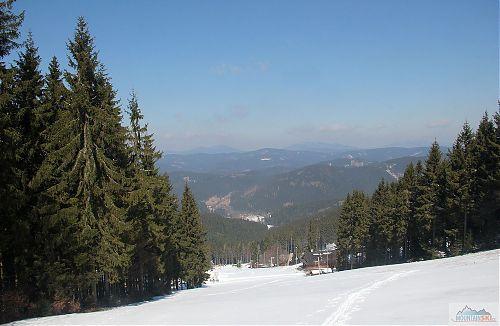 Horní část sjezdovky na Kasárnách a mé běžkařské cik-caky, v pozadí je vidět Kněhyně, Smrk a Lysá Hora