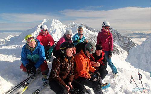 Vysmátí lyžníci na vyhlídkovém vrcholu